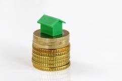 Monedas y casa modelo Imagen de archivo libre de regalías
