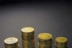 Monedas y centavos euro en fondo negro Fotos de archivo