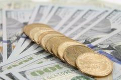 Monedas y cientos dólares Foto de archivo libre de regalías