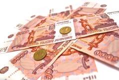 Monedas y cinco mil rublos de billetes de banco Imagenes de archivo