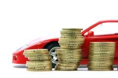 Monedas y coche rojo Imagen de archivo libre de regalías
