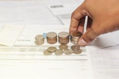 Monedas y cuenta con el ahorro de la mano para la vida Foto de archivo