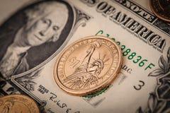 Monedas y cuentas de un dólar Fotos de archivo libres de regalías