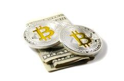 Monedas y dólares de EE. UU. brillantes de Bitcoin de la plata y del oro en la parte posterior del blanco Fotos de archivo libres de regalías