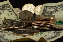 Monedas y dólares de los E.E.U.U. en una pila Foto de archivo libre de regalías
