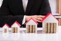 Monedas y diverso modelo Front Of Businessman de la casa de los tamaños fotos de archivo libres de regalías
