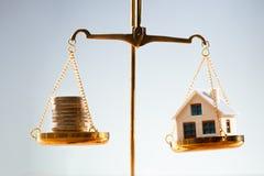 Monedas y escala apiladas de Balancing On Justice del modelo de la casa fotos de archivo