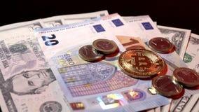 Monedas y euro de Bitcoin en los billetes de banco del dólar y del euro en un fondo brillante negro metrajes