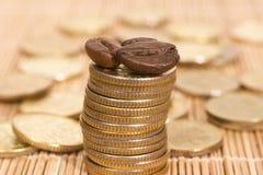 Monedas y granos de café Imagen de archivo