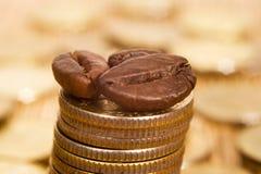 Monedas y granos de café Fotografía de archivo libre de regalías