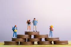 Monedas y grupo figuras miniatura del viajero de mini con el soporte de la mochila y de caminar en pasaporte imagen de archivo libre de regalías