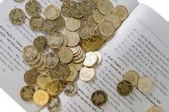 Monedas y libro Fotos de archivo