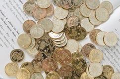 Monedas y libro Imagenes de archivo