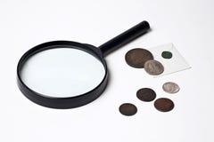 Monedas y lupa viejas Fotografía de archivo libre de regalías