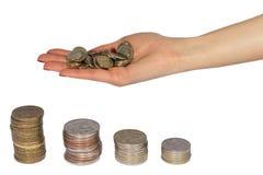 Monedas y mano en el fondo blanco Imagen de archivo