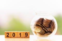Monedas y palabra 2019 del bloque de madera en fondo de la naturaleza ahorro del dinero imagenes de archivo