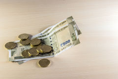 Monedas y 500 rupias de notas sobre la tabla de madera Fotos de archivo