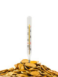Monedas y termómetro Fotos de archivo