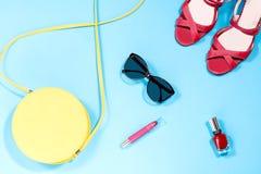 Monedero amarillo redondo, esmalte de uñas rojo, lápiz labial rojo, sandalias rojas, gafas de sol en un fondo azul en colores pas Fotos de archivo
