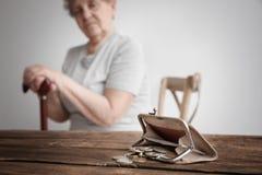 Monedero con las monedas y la mujer mayor borrosa foto de archivo