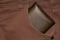 Monedero del cuero de Brown en el bolsillo Cartera a medio camino hacia fuera de una parte posterior de los vaqueros Tejanos con  Imagen de archivo libre de regalías