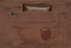 Monedero del cuero de Brown en el bolsillo Cartera a medio camino hacia fuera de una parte posterior de los vaqueros Tejanos con  Foto de archivo libre de regalías