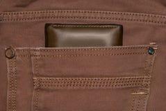 Monedero del cuero de Brown en el bolsillo Cartera a medio camino hacia fuera de una parte posterior de los vaqueros Tejanos con  Foto de archivo