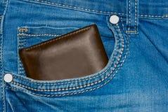 Monedero del cuero de Brown en el bolsillo Cartera a medio camino hacia fuera de una parte posterior de los vaqueros Tejanos del  Fotos de archivo libres de regalías