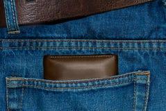 Monedero del cuero de Brown en el bolsillo Cartera a medio camino hacia fuera de una parte posterior de los vaqueros Tejanos del  Imagenes de archivo