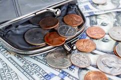 Monedero negro con los centavos en el fondo de las cuentas del ciento-dólar Imagen de archivo libre de regalías