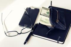 Monedero negro del ante con los dólares que pegan fuera de él el cuaderno, el smartphone, los vidrios y la pluma en el fondo blan fotografía de archivo