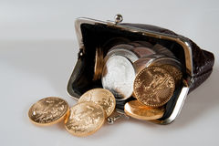 Monedero por completo de monedas de la plata y de oro foto de archivo