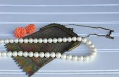 Monedero retro de la malla del vintage con pendientes anaranjados y un collar de la perla fotografía de archivo libre de regalías