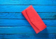 Monedero rojo de moda en un fondo de madera azul Visión superior Tendencia del minimalismo Fotografía de archivo