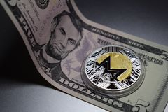 Monero cryptocurrency coin on a five dollar bill stock photography