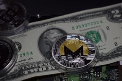 Monero cryptocurrencymynt på räkning för dollar två och datorbräde royaltyfria bilder