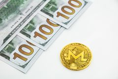 Monero and 100 dollars. Golden Monero coin xmr and 100 dollars bills on a white background Royalty Free Stock Photos