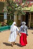 Monestery Saint Franciscus in Semarang. Semarang, Indonesia - November, 01, 2017:  A muslim woman and a catholic sister walkin hand in hand in  Monastery Saint Stock Photos