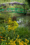 Monet's Garden Bridge. The bridge in Monet's garden in Giverny, France, with colorful spring flowers in the foreground Royalty Free Stock Photos