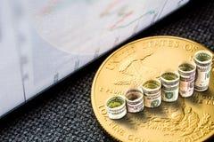 Moneta americana dorata dell'aquila con i dollari che formano i punti in aumento Immagini Stock