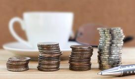 Moneta brogująca, filiżanka kawy, szkła i pióro na biurku, Biznes a Fotografia Royalty Free