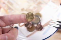 Moneta 10 centów na palcu wskazującym samiec oddaje białego talerza z pieniądze i metalu rozwidleniem zdjęcie royalty free
