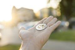 Moneta d'argento dorata dell'ondulazione a disposizione su un fondo vago di tramonto Mano che tiene i soldi virtuali di valuta cr Immagine Stock Libera da Diritti