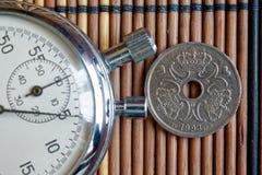 Moneta danese con una denominazione della corona scandinava due e del cronometro sulla tavola di legno - lato posteriore fotografia stock