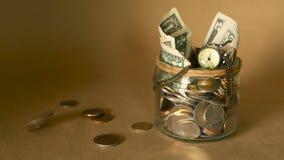 Moneta dei soldi di risparmio in barattolo Simbolo di investimento, tenente concetto dei soldi Raccolta delle banconote dei conta archivi video