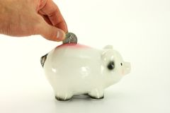 Moneta del deposito nella Banca Piggy isolata su bianco fotografia stock