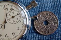 Moneta della Danimarca con una denominazione 5 della corona scandinava (corona) e del cronometro sul contesto blu consumato del d immagine stock libera da diritti
