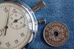 Moneta della Danimarca con una denominazione 2 della corona scandinava (corona) e del cronometro sul contesto blu consumato del d immagine stock libera da diritti