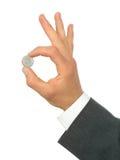Moneta della holding della mano dell'uomo d'affari Immagine Stock