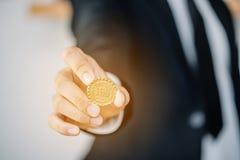 Moneta della tenuta dell'uomo di affari Immagini Stock